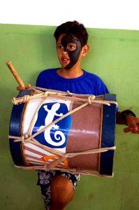 Crianca tocando instrumento de percussao