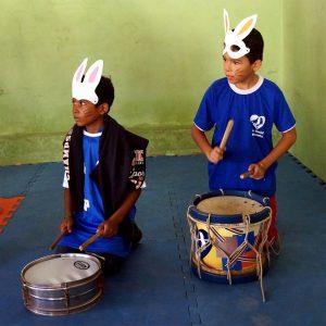 Criancas tocando dois tambores